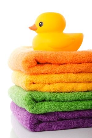 lavander�a: Pila de toallas de colorido y pato de goma amarillo aislados en blanco