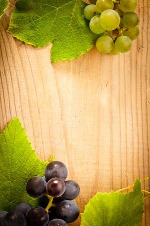 vid: Diferentes tipos de uva con hojas verdes en la mesa de madera