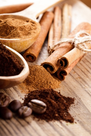 Coffee beans and cinnamon milled closeup in wooden spoons photo