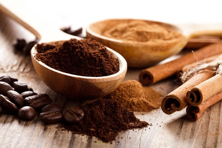 milled: Coffee beans and cinnamon milled closeup in wooden spoons Stock Photo