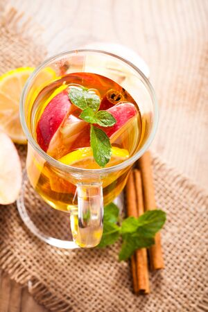 Apple, cinnamon and citrus beverage with twig of mint photo