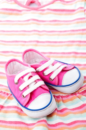 Pink baby footwear - gymshoes on dress photo