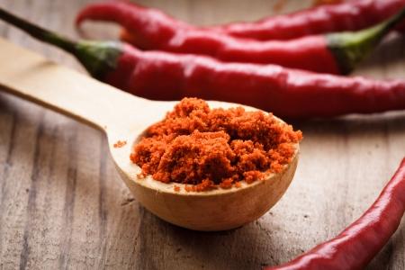 pimenton: Pimiento rojo picante caliente en una cuchara de madera sobre la mesa