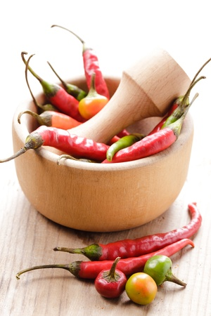 Red hot chilli pepper in wooden mortar on table photo