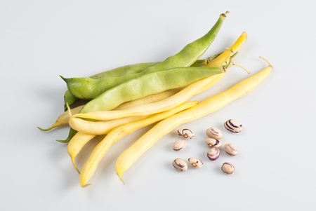 green and yellow string beans over white background photo