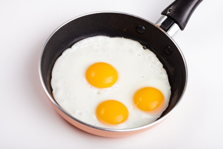 three fried egg on teflon pan without oil isolated on white photo