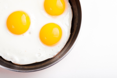 yolks: three fried egg on teflon pan without oil isolated on white