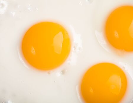 three ried eggs closeup background photo