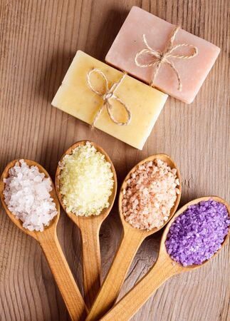 Various types of spa sea salt and soap in wooden spoons closeup photo