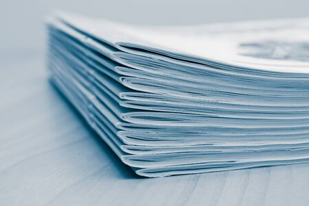 blank newspaper: Stack of white journals on table, closeup blue toned