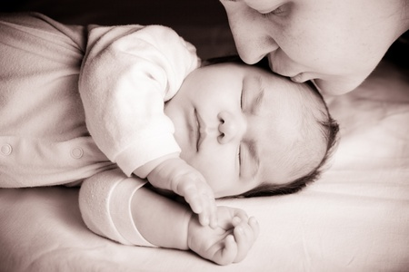 Sleeping newborn baby closeup face with mother kissing photo