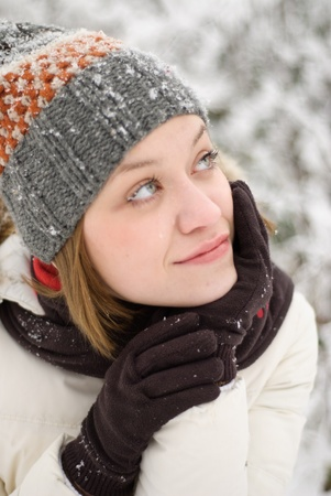 Girl with blue eyes warm oneself under snow outdoors. Close up portrait photo