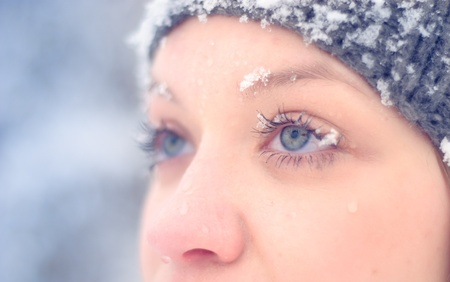 Girls face under snow outdoors. Close up portrait photo