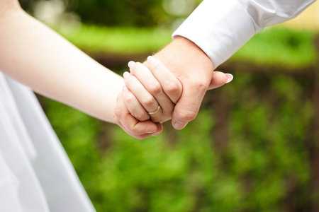 Bride and groom are holding hands each other photo