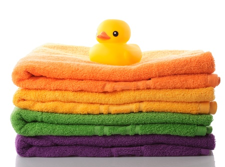 yellow duck: Stack of colorfull towels and yellow rubber duck isolated on white
