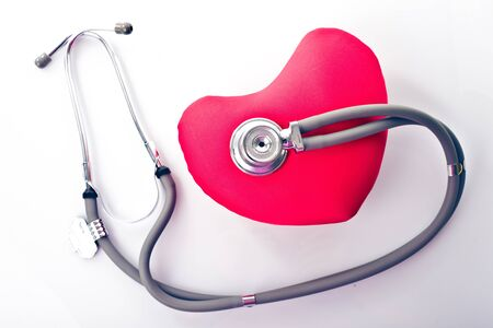 Medical stethoscope with red heart isolated on white photo