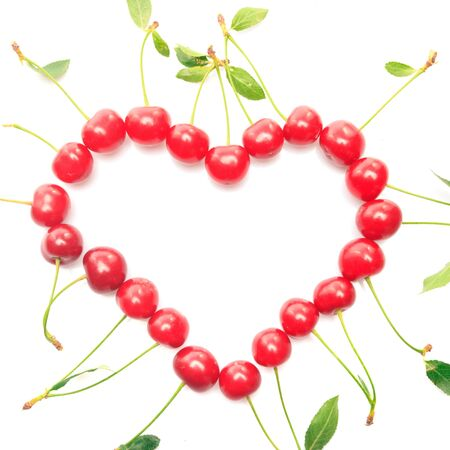 Heart shape from cherries with green leaves isolated on white photo