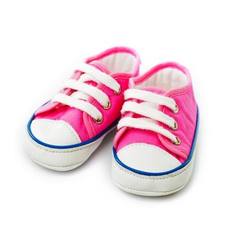 スニーカー: ピンクのベビー シューズ - 白で隔離される gymshoes 写真素材