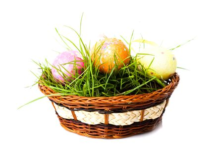Three colorfull easter eggs on green grass in basket isolated photo