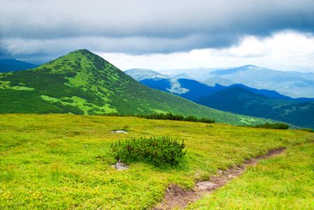 Path in mountains in storm day photo
