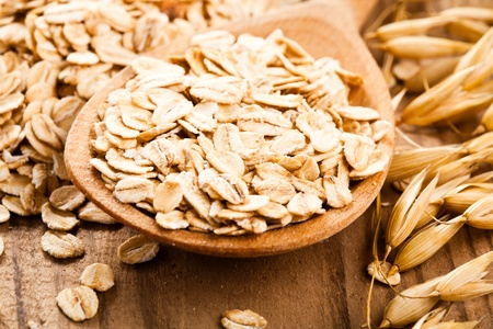 Oat flakes in spoon on wooden table photo