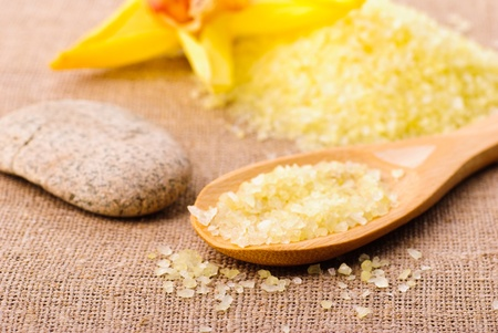 yellow bathing salt in the wooden spoon, spa concept photo