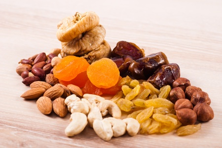 Dried fruits and nuts heaps on wooden table