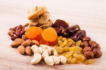 fichi: Frutta secca e cumuli di dadi sul tavolo in legno Archivio Fotografico