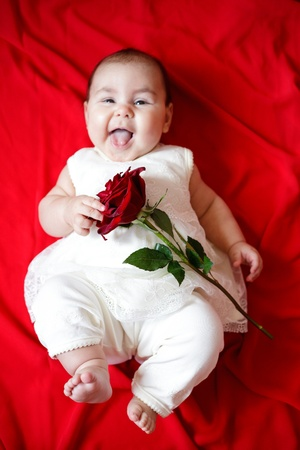 Cute little girl in white dress with red rose photo