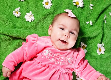 Adorable baby girl lying down on meadow and smile Stock Photo - 13107138