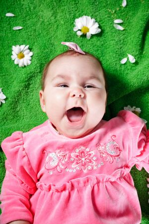 Adorable baby girl lying down on meadow and smile Stock Photo - 13107135