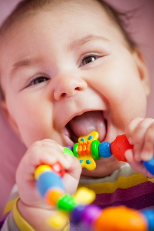 teething: Smiling and playing baby with teething ring. Closeup face.