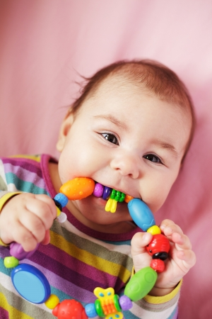 Smiling and playing baby with teething ring. Closeup face. photo