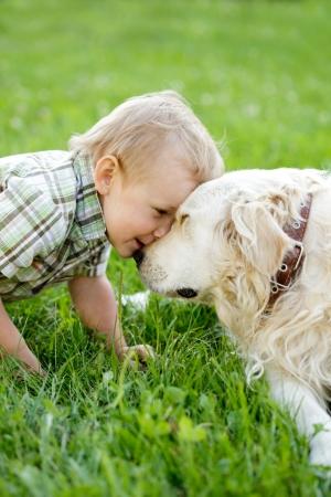 perro labrador: Ni�o lindo chico rubio con el perro perdiguero de oro al aire libre Foto de archivo