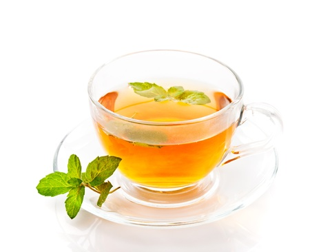goodness: Glass cup of tea with mint isolated on white