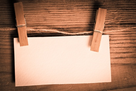 clothespin with blank white card on the wooden backgorund photo