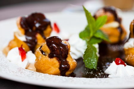 Profiteroles with ice cream and chocolate on plate photo