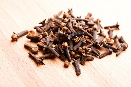 dried spice: Los clavos de especias esparcidas en la mesa de madera