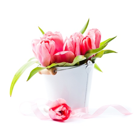 Pink tulips in decorative bucket closeup photo