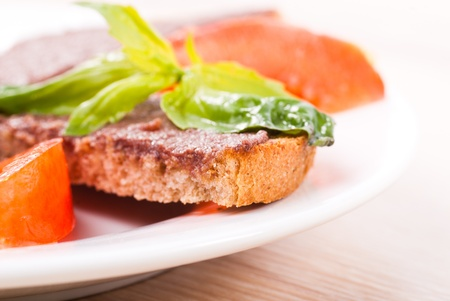 Crostinis with olive tapenade, basil and tomato on plate photo