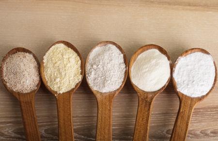 abastecimiento: Varios tipos de harina en cinco cucharas de madera Foto de archivo