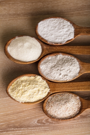 maize flour: Various types of flour in five wooden spoons Stock Photo