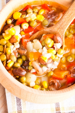 Minestrone soup in wooden bowl closeup. Traditional italian dish photo
