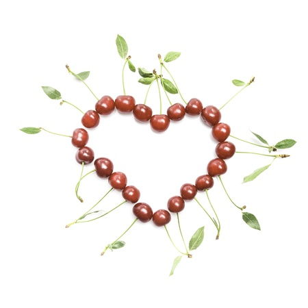 The heart shape from cherries with green leaves photo