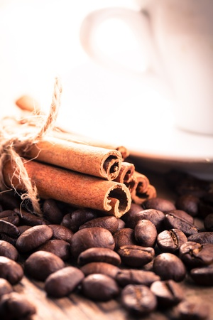 Coffee beans and cinnamon sticks close up photo