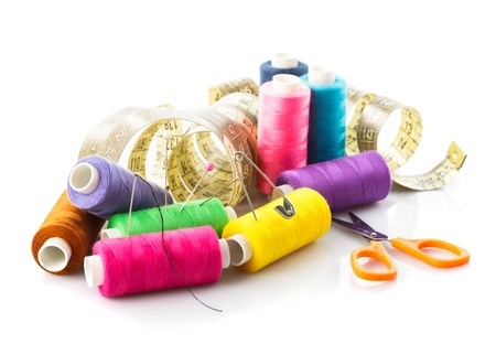 Sewing items  multicoloured threads, pins, meter and scissors on white photo