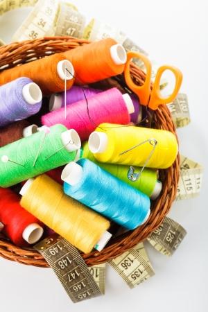 hilo rojo: Art�culos de coser en las discusiones canasta, alfileres, tijeras y metros en blanco Foto de archivo
