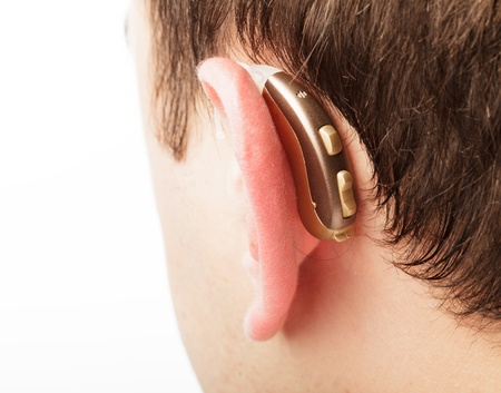 deafness: Hearing aid on the man s ear closeup