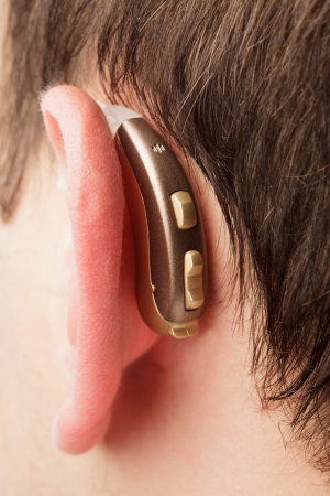 auditory: Hearing aid on the man s ear closeup
