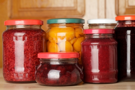Sweet preserves as jams and compotes on table in kitchen photo